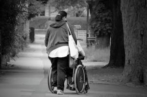 Pflegepersonal Frau schiebt Person in Rollstuhl